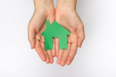 Hands holding paper house figure on white background. Real Estate green house Concept. Ecological building. Top view.