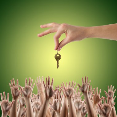REAL ESTATE concept. Many hands want to get the key, reaching out for key - concept of winning a house, apartment. Close up view of hand holding key to a dream house. Clipping pass and copy space. Green background