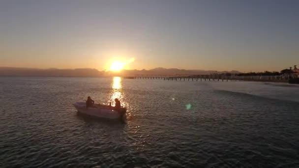 Napkelte a tengerben, egy halász lebeg egy kis motorcsónak felé. Nyugalom, napsugár.