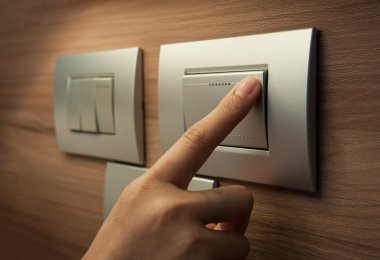 finger is turning on a grey light switch.