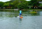 Ein Bilderbuchpaar am Morgen beim Paddelbrettspielen am See.