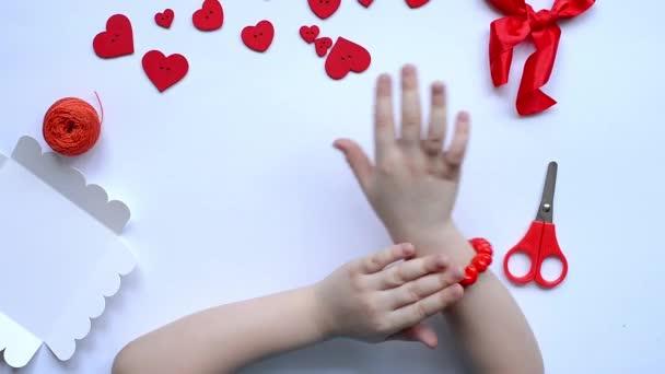 DIY náramek z červených korálků ručně vyrobený pro dívku na ruce na Valentýna. ručně vyrobená dětská dekorace. koncept řemeslné výroby. krok 6. Rozvržení, horní pohled