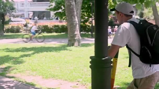 muž v čepici a bílém tričku s batohem jezdí na elektrickém skútru v parku. Koncept pronájmu elektrických vozidel