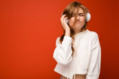 Beautiful happy positive young blonde woman wearing white hoodie isolated over colourful background wearing white wireless bluetooth headphones listening to music and dancing
