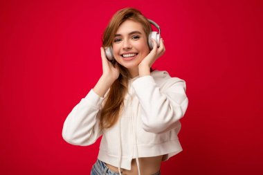 Photo of beautiful happy smiling young blonde woman wearing white hoodie isolated over colourful background wall wearing white wireless bluetooth earphones listening to cool music and enjoying looking