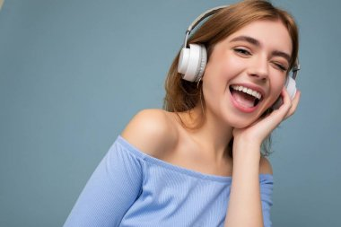 Closeup photo of attractive happy smiling young blonde woman wearing blue crop top isolated over blue background wall wearing headphones listening to music and having fun