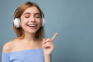 Closeup photo of beautiful positive smiling young blonde woman wearing blue crop top isolated over blue background wall wearing white wireless bluetooth earphones listening to cool music and enjoying