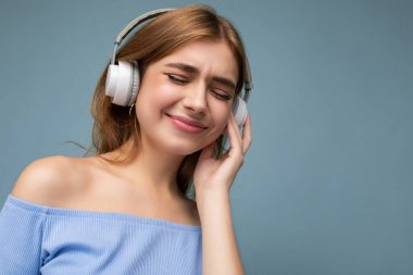 Closeup portrait photo of beautiful positive smiling young blonde woman wearing blue crop top isolated over blue background wall wearing white wireless bluetooth headphones listening to good music and
