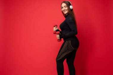 Side-profile photo of attractive positive smiling young brunette woman wearing black sport clothes isolated on red background wall doing fitness using dumbbells wearing white bluetooth earphones