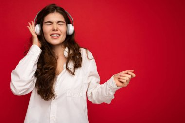 Attractive emotional young brunette female person wearing white shirt and optical glasses isolated over red background wearing white wireless bluetooth earphones listening to music with sincere