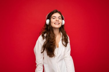 Attractive happy smiling young brunette female person wearing white shirt and optical glasses isolated over red background wearing white wireless bluetooth earphones listening to music and looking at
