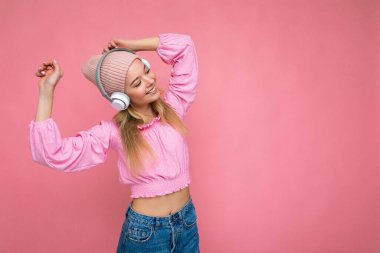Beautiful happy smiling young blonde woman wearing pink blouse and pink hat isolated over pink background wall wearing white wireless bluetooth headphones listening to cool music having fun and