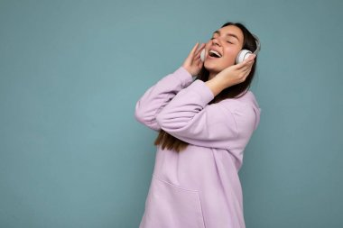 Pretty positive smiling young brunette woman wearing light purple hoodie isolated over blue background wall wearing white bluetooth headphones listening to good music and moving having fun