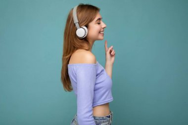 Side-profile photo of beautiful positive smiling young blonde woman wearing blue crop top isolated over blue background wall wearing white wireless bluetooth earphones listening to cool music and