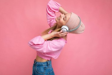 Side-profile photo of beautiful happy smiling young blonde woman wearing pink blouse and pink hat isolated over pink background wall wearing white wireless bluetooth headphones listening to cool music