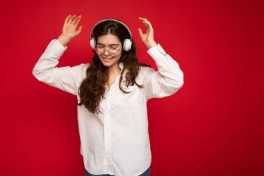 Attractive happy smiling young brunette female person wearing white shirt and optical glasses isolated over red background wearing white wireless bluetooth earphones listening to music and dancing