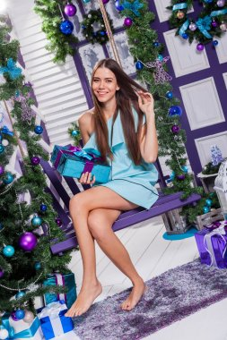brunette in a turquoise dress sitting on a swing next to a Chris
