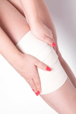 girl on a white background corrects an elastic bandage which tie