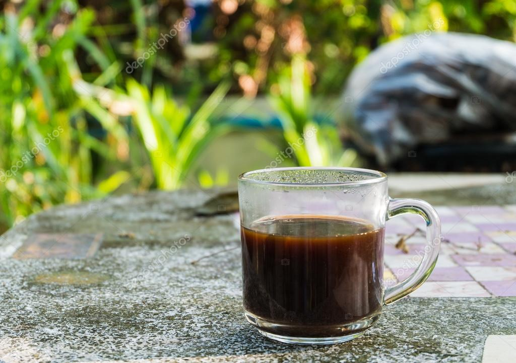 Cup of black coffee on the stone table and Green leaf background