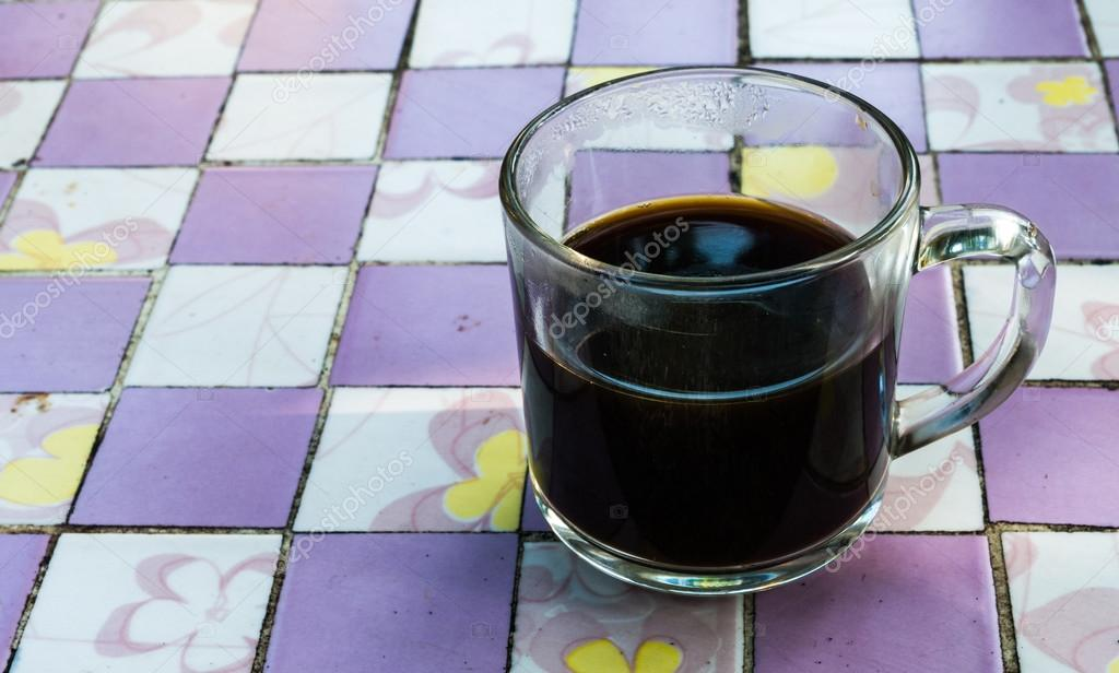 Cup of black coffee on a square checkerboard pattern.