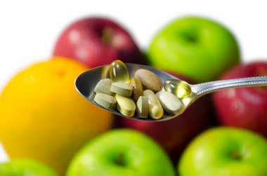 Assorted vitamins and nutritional supplements in serving spoon.
