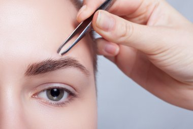 Young woman with short hair plucking eyebrows tweezers close up
