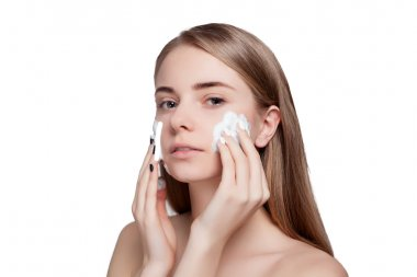 Beautiful woman cleaning face with foam treatment light background