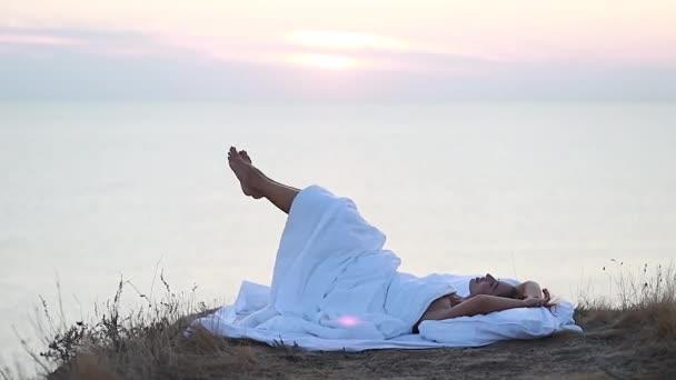 mladá žena stojící zabalená bílá přikrývka útes vrchol s výhledem na moře hledá krásný večer pěkný západ slunce teplé záře horizont pozadí zpět plný pohled léto podzim divoká příroda sama.
