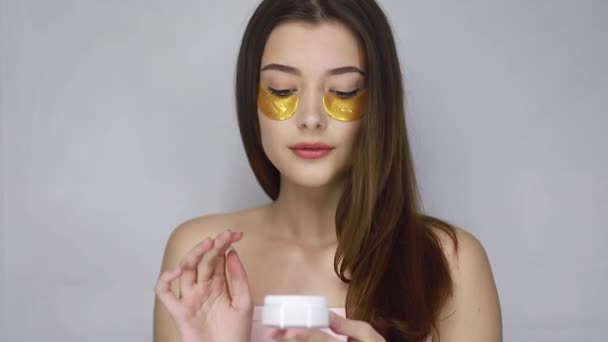 beauty, people and health concept - Nude portrait of amazing brunette woman putting eye gold patches under eyes for greater and fresher look. Beautiful model fashion girl posing smiling on camera.