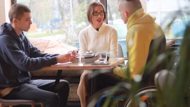 Kafedeki tekerlekli sandalyedeki mutlu genç adam arkadaşlarıyla iletişim kuruyor. Çeşitli takımlar kafede birlikte çalışıyor, bir online teknoloji firması pazarlama stratejisi için beyin fırtınası yapıyorlar..