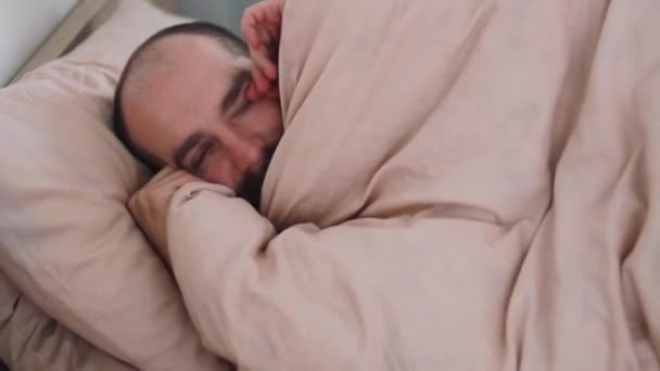 Ospalý unavený muž s kocovinou se probudí v posteli, portrét detailní. Mladý muž s bolestí hlavy ráno po probuzení. Unavený nemocný chlap. modré pozadí tapety.