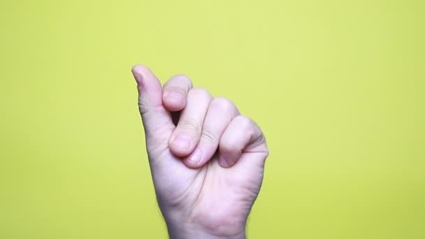 Mann Hand schnippt ihre Finger zu Musik Rhythmus Geste isoliert über gelbem Hintergrund im Studio. Kopierfläche für Werbung. Mit Platz für Text oder Bild. Werbefläche, Attrappe.