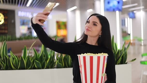 Young Girl is Sitting in the Cafe Before the Film She Eats Popcorn. selfie time. the girl takes a selfie on the phone to post it on social networks