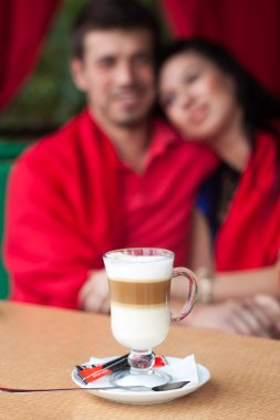 Couple holding hands and drinking coffee in cafe outdoors