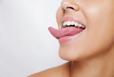 Beautiful woman sticking out her tongue and showing young piercing