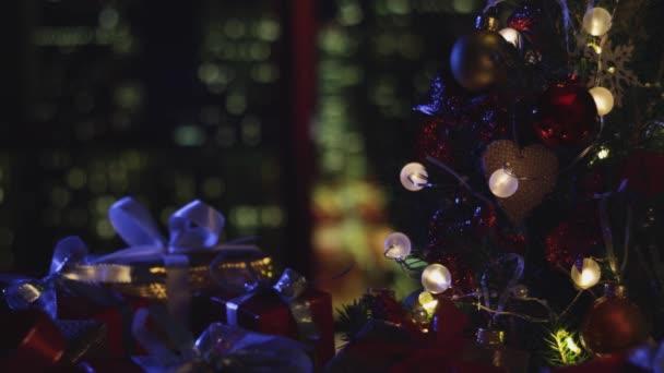 Nový rok vánoční pozadí. Vánoční stromek. Noční město v okně. Dekorace, červené zlaté koule a zářící žárovky na stromě. Teplá domácí nálada. Hloubka pole, měkké soustředění. Červená kamera 4K
