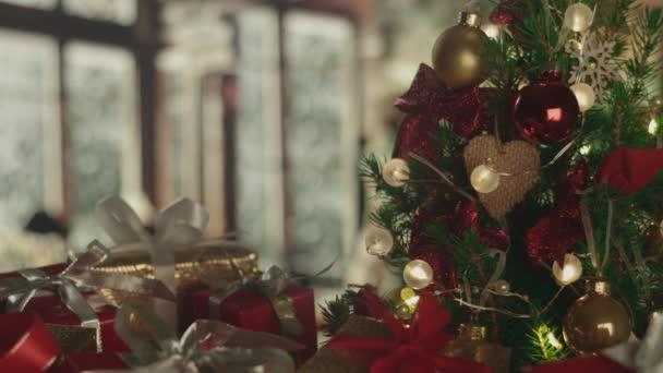 Nový rok vánoční pozadí s mrazivým oknem a padající sníh na pozadí. Vánoční stromek, dárky. Dekorace, červené zlaté koule, zářící žárovky. Teplá domácí nálada. Hloubka pole. Červená kamera 4K
