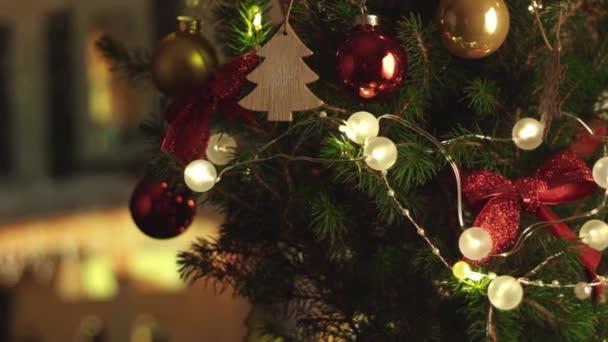 Nový rok vánoční slavnostní zázemí s vánoční dům na pozadí. Vánoční stromek. Dekorace, červené zlaté koule a zářící žárovky na stromě. Teplá domácí nálada. Hloubka pole. Točí se. 4K