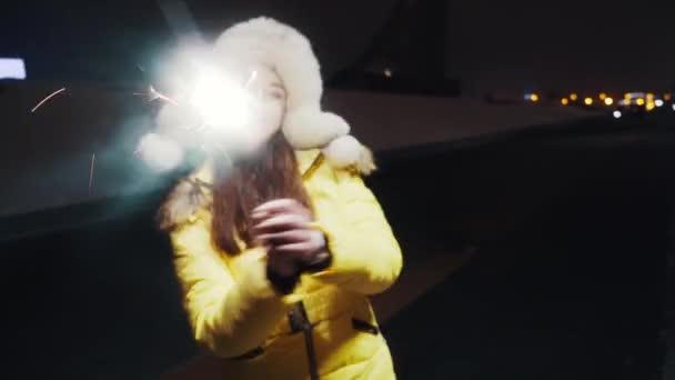 Fiatal, aranyos lány télikabátban és sárga dzsekiben ünnepi hangulatban. Ragyogó égő csillagszórók a kezükben repülő szikrákkal. Tánc és szórakozás. Ünnepi ötlet. Mozgó kamera