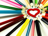 Barevné dřevěné pastelky a červené srdce