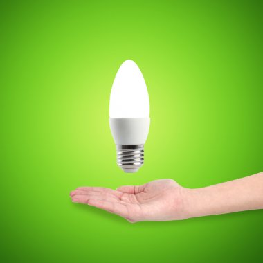 Glowing LED energy saving bulb in a hand on a green background