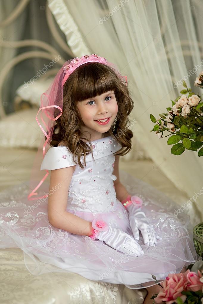 Das kleine Mädchen in einem Abendkleid auf einem Bett — Stockfoto ...
