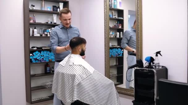 Young man in barber shop sits in an armchair. Barber cuts his hair with a trimer
