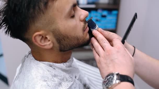 Der Meister gibt die Kontur des Haarschnitts vor. Herrenfrisur im Friseursalon.