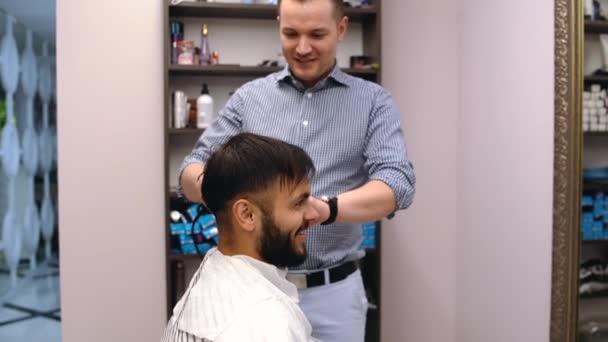 Junge hübsche Friseurin macht Haarschnitt eines attraktiven bärtigen Mannes im Friseursalon.