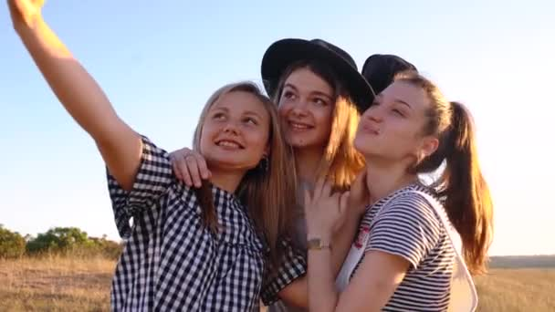 Three cheerful young women take selfies in nature
