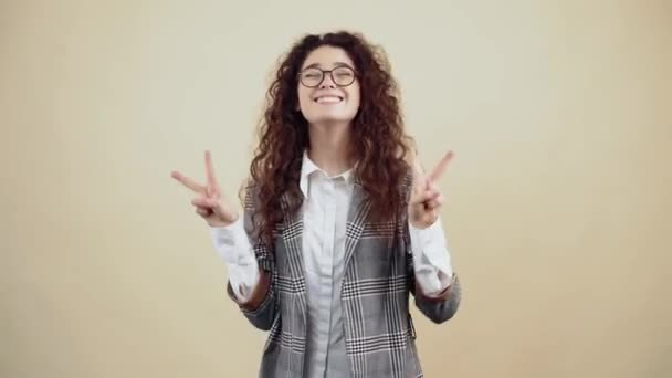 The cheerful young woman with her teeth out shows the gesture of peace with both hands.