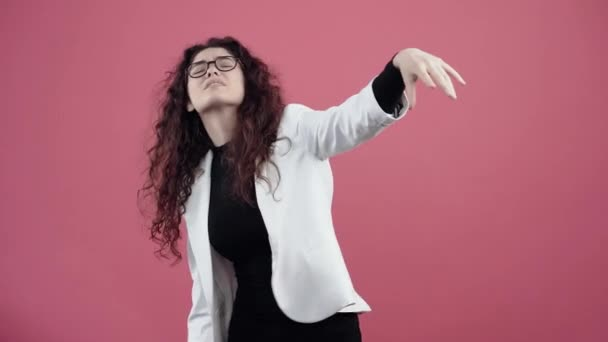Angry young woman with curly hair, she looks with her hand to push away because she cant see. Young hipster in white jacket and black shirt, with glasses posing isolated on pink background in the