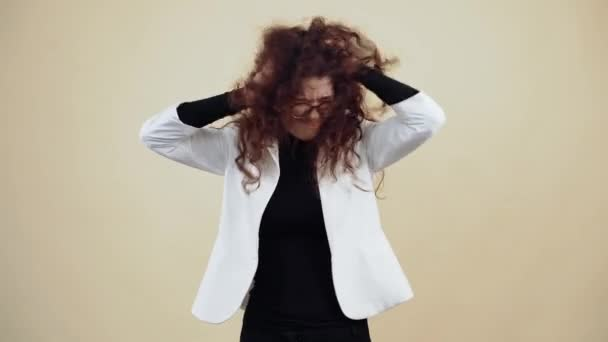 The angry young woman, agitated with curly hair, shakes her hair with her hands and shouts desperately. Young hipster in gray jacket and white shirt,