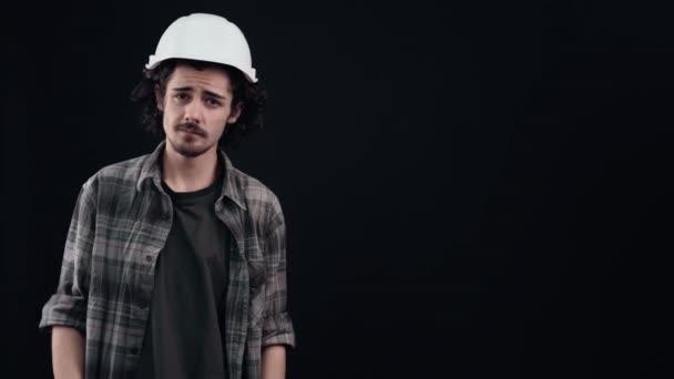 Charismatický chlapec v bílé přilbě inženýra ukazuje doprava, říká ne a projevuje známky nelibosti. Izolované na černém pozadí. Pojem život. Lidské emoce. 4k portrét